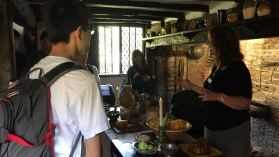 コテージのキッチンにてガイドより説明を受ける生徒たち。