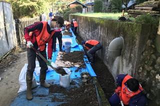 水路から泥を掻き出し、土嚢に詰めます。